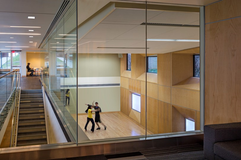 At the University of Michigan, a floor above what had been a mechanical support space was removed, creating both a day-lit two-story dance studio and a two-story lounge with glass windows, bringing natural light into what was once a dark utility space.